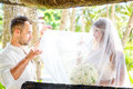Beautiful young bride in the veil with wedding bouquet of white roses and groom on tropical beach summer vacation concept Stock Photos