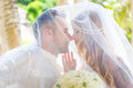 Beautiful young bride in the veil with wedding bouquet of white roses and groom on tropical beach summer vacation concept Royalty Free Stock Photos