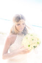 Beautiful young bride in the veil with wedding bouquet of white roses on tropical beach summer vacation concept Royalty Free Stock Image