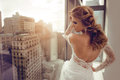 Beautiful Young bride in wedding dress posing near window Royalty Free Stock Photo