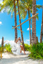 Beautiful young bride in a white dress sits on a swing under a p palm tree tropical beach summer vacation Royalty Free Stock Photos