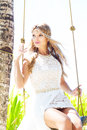 Beautiful young bride in a white dress sits on a swing under a p palm tree tropical beach summer vacation Royalty Free Stock Image