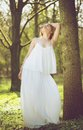 Beautiful young bride in white wedding dress posing against tree portrait of a Royalty Free Stock Photos