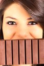 Beautiful young brunette girl eating chocolate bar closeup of smilling big Royalty Free Stock Photo