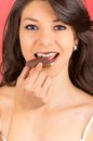 Beautiful young brunette girl eating chocolate bar smilling with brown lips Royalty Free Stock Photography