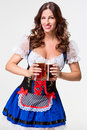 Beautiful young brunette girl of oktoberfest beer stein in dirndl drinks out on white background Royalty Free Stock Images