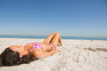 Beautiful young brunette in pink bikini sunbathing on the beach Royalty Free Stock Photo