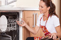 Beautiful young brunette washing dishes attractive housewife taking from dishwasher Royalty Free Stock Images