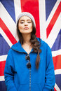 Beautiful young brunette woman with british flag in stylish clothes and sunglasses national in background outdoors lifestyle Royalty Free Stock Image