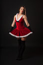 Beautiful young brunette woman dressed as santa studio shot black background Stock Photography
