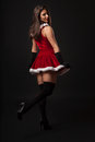 Beautiful young brunette woman dressed as santa studio shot black background Stock Photos