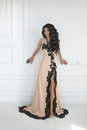 Beautiful young brunette woman in elegant dress with long wavy h