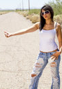 Beautiful young brunette woman hitchhiking Royalty Free Stock Photo