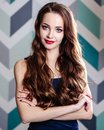 Beautiful young brunette woman with long curly hair and evening makeup, fashion beauty portrait Royalty Free Stock Photo
