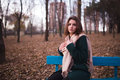 Beautiful young brunette woman sitting on a bench in autumn park Royalty Free Stock Photo