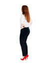Beautiful young business woman looking at wall rear view isolated over white slim girl in office clothes holding hands on waist Stock Photos