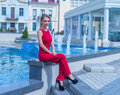 Beautiful young business woman sitting at the city square