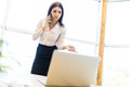 Beautiful young business woman sitting near office desk and talking on cell phone Royalty Free Stock Photo