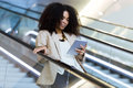 Beautiful young business woman using her digital tablet on escalator. Royalty Free Stock Photo