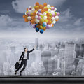 Beautiful young businesswoman flying with balloons over cityscape Royalty Free Stock Images