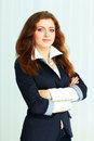 Beautiful young businesswoman standing with arms folded at office Royalty Free Stock Photo
