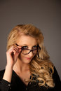 Beautiful young caucasian blond woman with eye glasses looking i into copy space Stock Photo