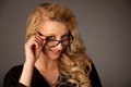 Beautiful young caucasian blond woman with eye glasses looking i into copy space Stock Image