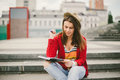 A beautiful, young Caucasian girl sitting on the street smile, the joy, sit with notebook and pen in Ruhi. In the red sweater, jea Royalty Free Stock Photo