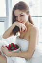 Beautiful young Caucasian woman with long hair sitting in bed early morning by window, eating red fresh strawberry Royalty Free Stock Photo
