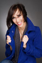 Beautiful young and confident woman laughing wearing dark blue winter coat studio portrait vertical color image of a Royalty Free Stock Photo