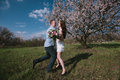 Beautiful young couple dancing and having fun on blue sky background in bloom garden lifestyle Royalty Free Stock Photo