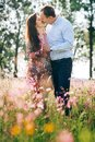 Beautiful young couple holding hands and kissing in sunshine in spring meadow with pink flowers. Happy family embracing in green Royalty Free Stock Photo