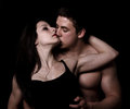 Beautiful young couple hugging and kissing isolated on black background Stock Photo