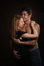 Beautiful young couple hugging and kissing isolated on black background Royalty Free Stock Photography