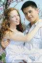 Beautiful young couple in love among the flowering trees one of pink Royalty Free Stock Photos