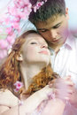 Beautiful young couple in love among the flowering trees one of pink Royalty Free Stock Image