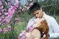 Beautiful young couple in love among the flowering trees one of pink Royalty Free Stock Images