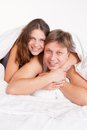 Beautiful young couple relaxing in bed at home over white Royalty Free Stock Image