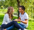 Beautiful young casual couple sitting on grss in a park. Royalty Free Stock Photo