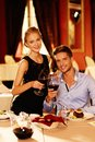 Beautiful young couple in restaurant with glasses of red wine luxury Stock Photography