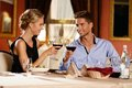 Beautiful young couple in restaurant with glasses of wine Royalty Free Stock Images