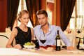 Beautiful young couple in restaurant with glasses of wine Stock Photos
