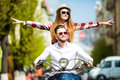 Beautiful young couple riding scooter together while happy woman raising arms and smiling Royalty Free Stock Photo