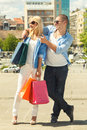 Beautiful young couple with shopping bags looking at camera Royalty Free Stock Photos
