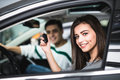 Beautiful young couple sitting at the front seats of their new car while woman showing keys and smiling Royalty Free Stock Photo