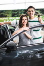 Beautiful young couple is smiling and looking at camera while leaning on their new car in a motor show. Man is holding car keys Royalty Free Stock Photo