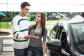 Beautiful young couple standing at the dealership choosing the car to buy. Man pointed on car. Royalty Free Stock Photo