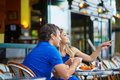 Beautiful young couple of tourists in Parisian street cafe Royalty Free Stock Photo