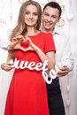 Beautiful young couple with words Sweet love showing the form of heart hands. Valentine's Day. Royalty Free Stock Photo
