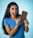 Beautiful young cute and happy latin woman in casual clothes holding big delicious chocolate tablet looking with temptation Royalty Free Stock Photo
